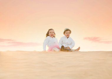 two adorable little kids sitting on top of sand dune
