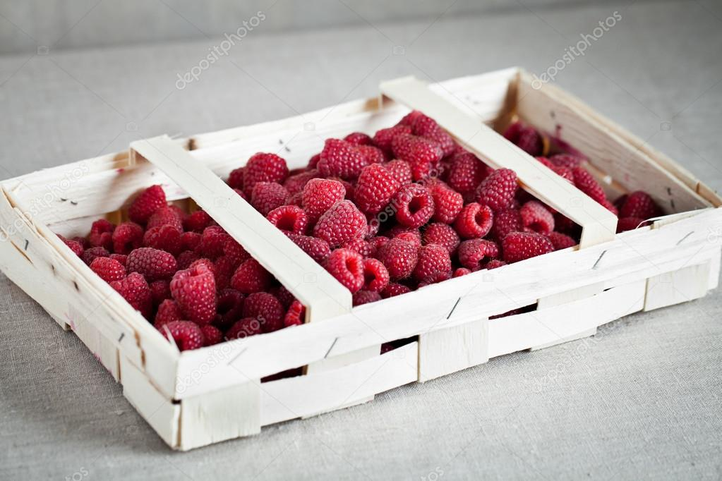 Box of raspberry on the table