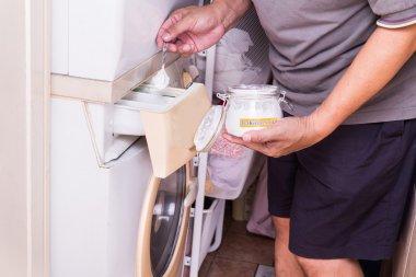 Person adding baking soda into washing machine to wash clothes