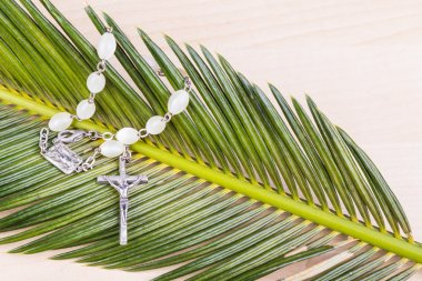 Closeup Catholic rosary with crucifix and beads on palm leaf