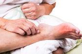 Muž na posteli objetí nohy bolestivé zduření dnu zánětu