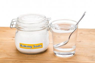 Baking soda in jar, spoonful and glass of water for multiple hol