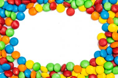 Frame of colorful chocolate candy on white background with space