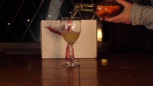 Ruční nalévání sklenice bílého vína s baleným vánočním dárkem
