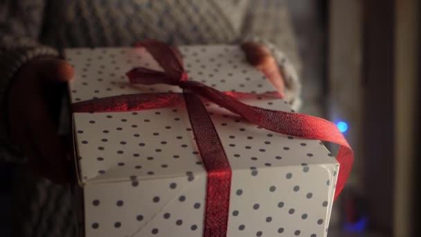 A kezek karácsonyi ajándékot adnak masniba csomagolva.
