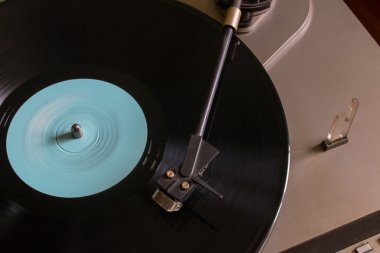 Rotating vinyl record with a blue mark on the turntable view from the top selective focus