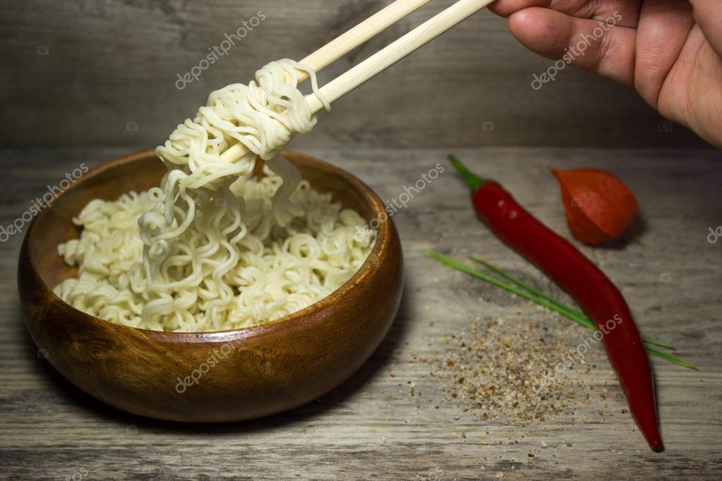 Instant noodles and red peppers on wooden background