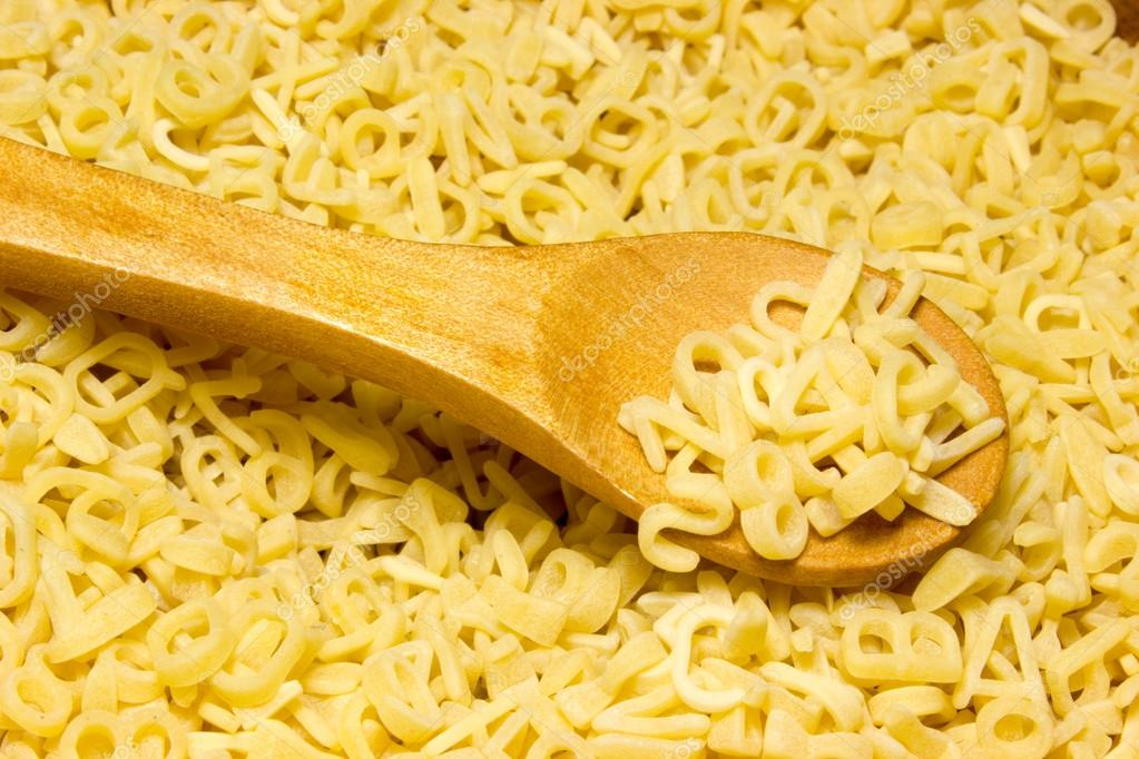 Noodle letters and wooden spoon on wooden background