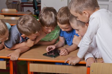 Primary school boys play with tablet pc