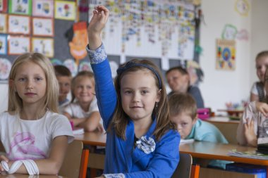 Primary school girl raises her hand