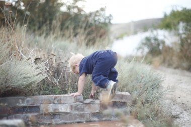 Child climbs up on border
