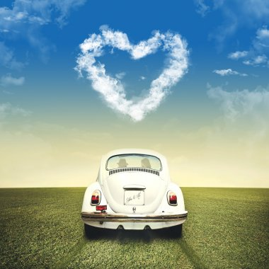 Couple in love driving on a white car under heart shape of clouds