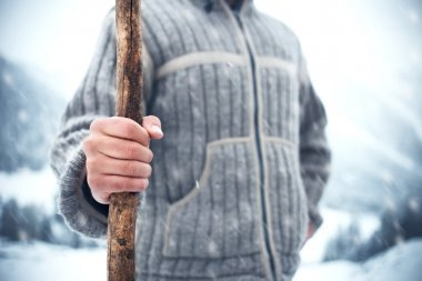 Man holding wood stick in the cold winter while snowing