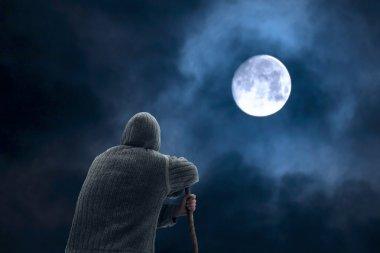 Climber Man contemplating the big white moon at night