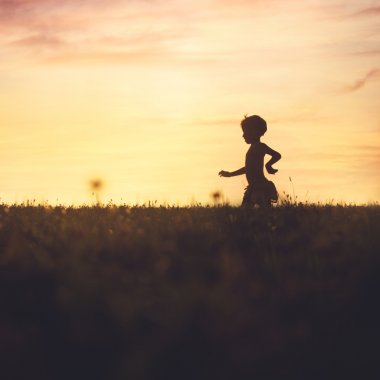 Carefree baby running in the field at sunset