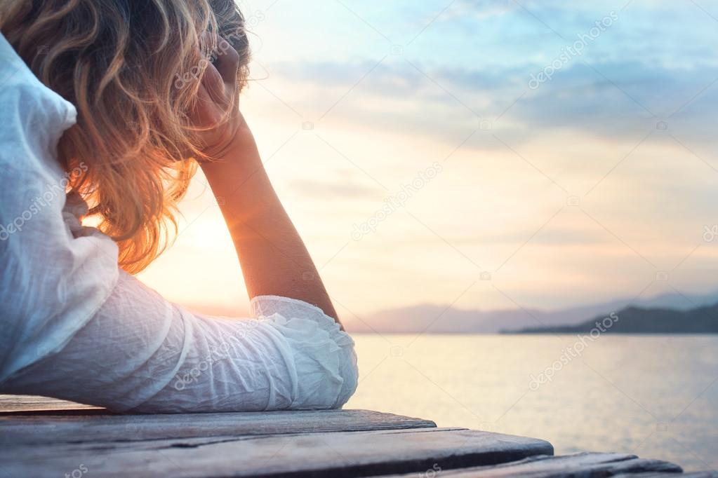 melancholy woman observing the sunset