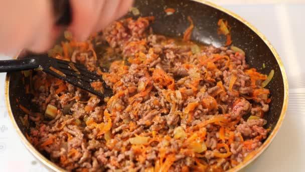 ve smažené pánvi smažené maso, cibuli a mrkev. Boloňská omáčka