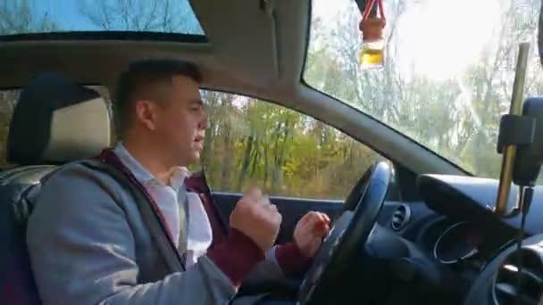 Ein Mann in grauer Jacke tanzt hinter dem Steuer eines Autos.