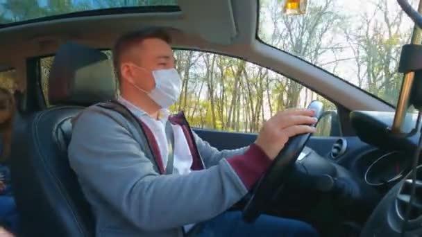 Ein Mann in grauer Jacke setzt sich hinter dem Steuer eines Autos eine Schutzmaske auf.