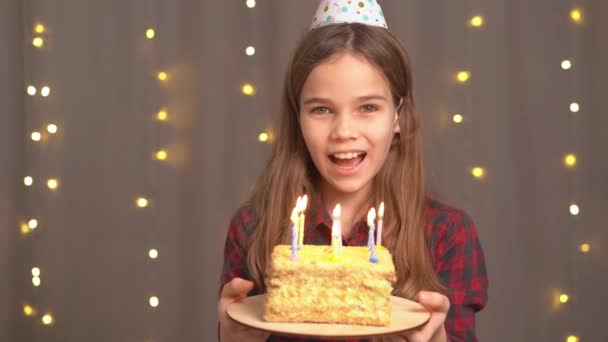 Boldog tini lány szülinapi tortával. hagyomány kívánni és elfújni a tüzet