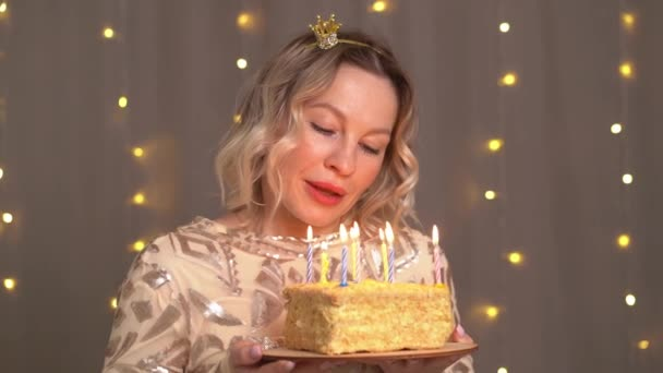 Schöne blonde Frau in kleiner Krone auf dem Kopf mit Geburtstagstorte und Kerzen.