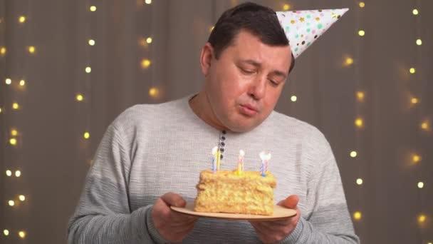 smutný muž ve slavnostní čepici s narozeninovým dortem sfoukne svíčky.smutek v důsledku stárnutí