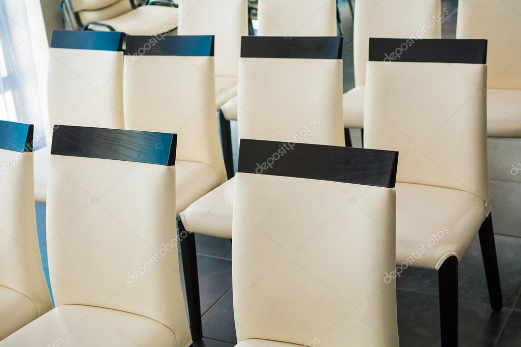Wit leren stoelen in een zaal voor conferenties en lezingen