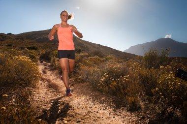 Blonde female trail runner running through a mountain landscape