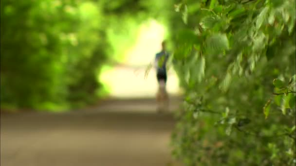 Out of focus woman running up country lane