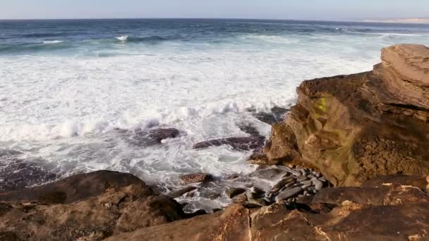 Waves crashing on rocks and beach in San Diego