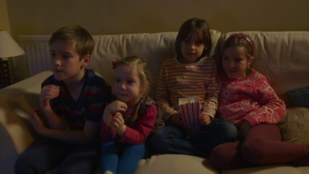 Skupina dětí sedí na pohovce a jíst popcorn při sledování Tv. Dolly