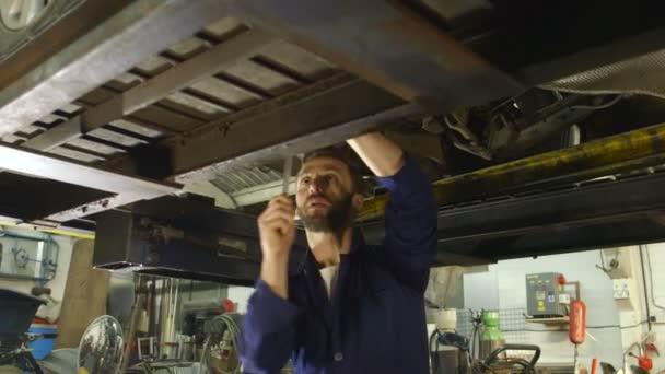 Mechanik kontrola dílů při práci pod autem
