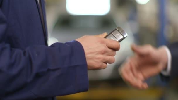 Zár-megjelöl szemcsésedik-ból egy szerelő átadása egy autó kulcs egy ember, egy öltöny