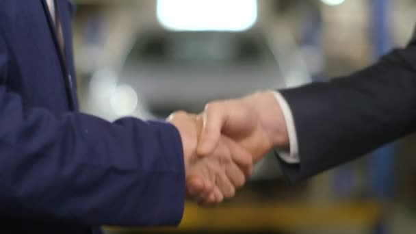 Close Up shot of mechanic and customer shaking hands in an auto repair shop