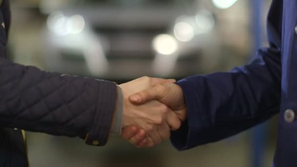 Close Up shot of mechanic and customer shaking hands in an auto repair shop.