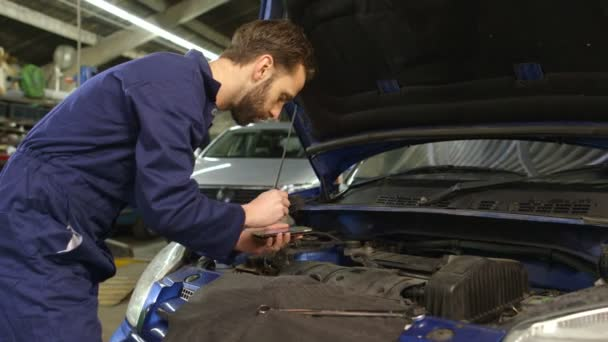 Mechanic entering data into a diagnostic tool while doing routine maintenance