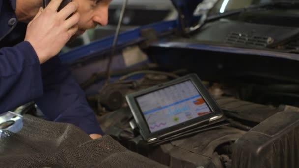 Mechanik, mluvit s majitelem auta na mobilní telefon