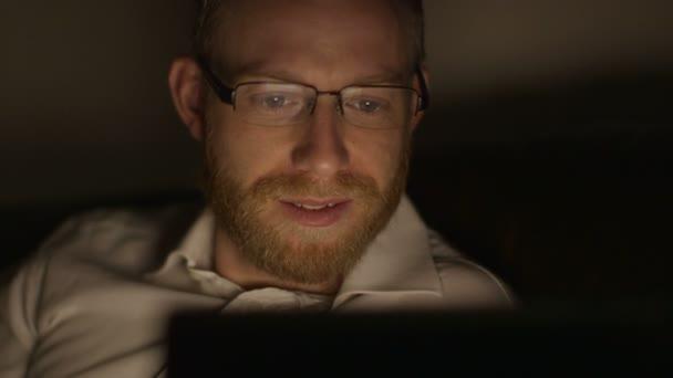 Fiatal üzletember élvezi egy filmet a tabletta egy kemény napi munka után