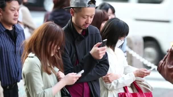 Tokyo, Japonsko - cca 2013: Lidé procházení Internetu při dojíždění do práce