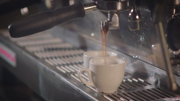 Two cups of coffee being poured from a espresso machine.
