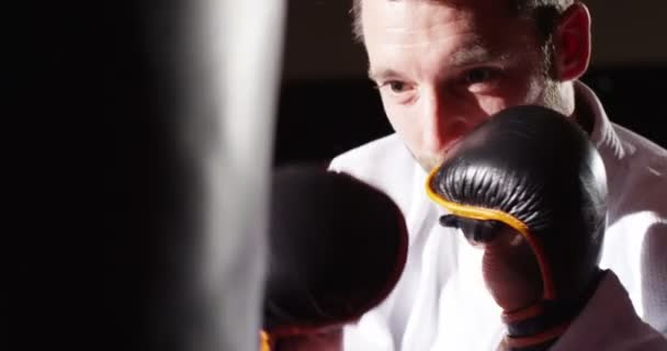 Closeup of a young athlete boxing with a punching bag in slow motion.