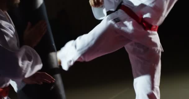 Mladý sportovec v kimonu kopy pytel v pomalém pohybu