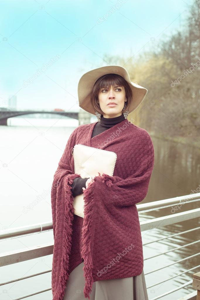 Pretty French Brunette Woman In Hat And Poncho Waiting Spring Near Lake Stock Photo