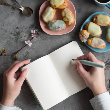Female two hands hold a empty note. Designer draws sketches at the table coffee break. Hands with ink pen writing on notebook. Bird eyes view. Pastel shades. Twig spring cherry blossom.