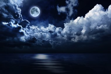 Full moon in night sky over water