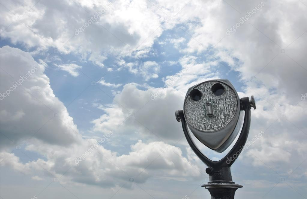 Coin-operated tourist binoculars aimed at a cloudy sky.