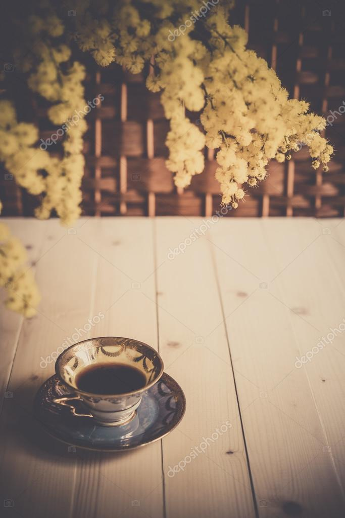 Cup of coffee on wooden table and mimosa
