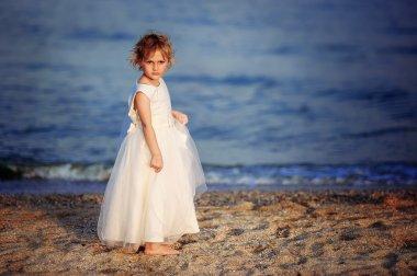 girl in a white dress walks on the sea beach