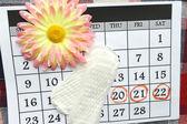 Fotografie Frauen Hygieneschutz, Close-up.Menstruation Kalender mit Baumwolle Tampons, orange Gerber, Sanitär-Pads auf rotem Hintergrund