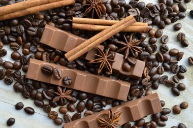 Bar of dark chocolate, milk chocolate bar, coffee beans, star anise, cinnamon sticks, seasonings, spices, close-up on a white wooden background